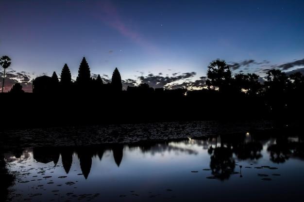 Angkor wat temple at sunrise reflecting in water Premium Photo