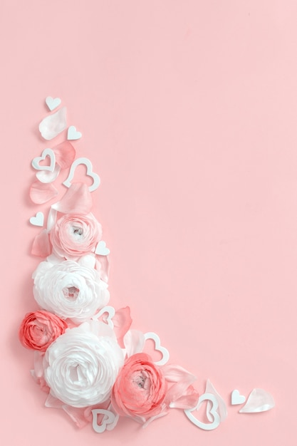 Angle frame made of ranunculus flowers, petals and hearts on a light pink top view Premium Photo