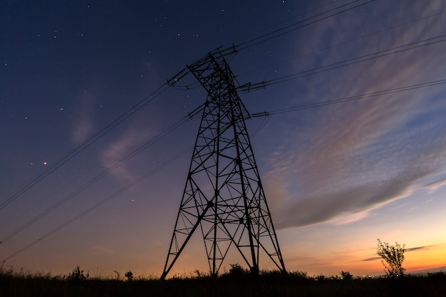 Angled view of high voltage tower with electric power lines stretching on dark blue starry sky Premium Photo