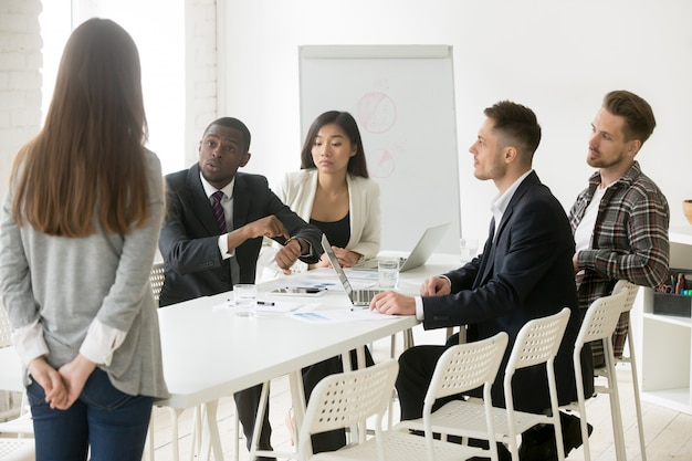 Angry african boss scolding employee for being late at meeting Free Photo