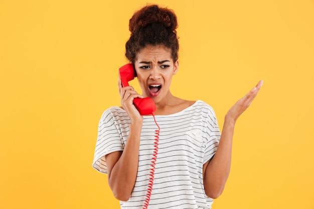 Сердитая африканская женщина кричит во время разговора по красному телефону Бесплатные Фотографии