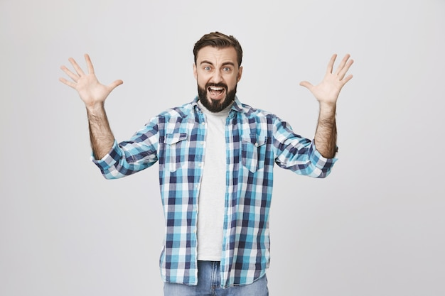 Angry aggressive guy shouting and raising hands up eccentric Free Photo