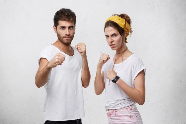 Злая агрессивная молодая кавказская пара, стоящая в оборонительной позиции, со сжатыми кулаками, с уверенным, решительным взглядом, готовая защитить себя и отстоять свои права Бесплатные Фотографии