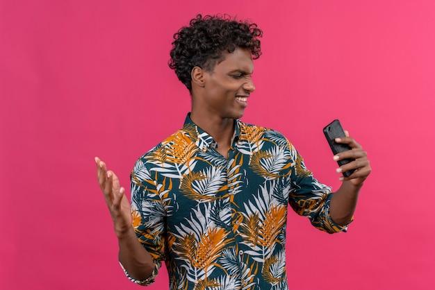 怒っている緊張した浅黒い肌の男の葉っぱのシャツに携帯電話を見て、手を上げる 無料写真