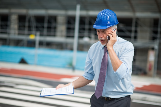 Angry architect talking on the cellphone in front of construction site Premium Photo