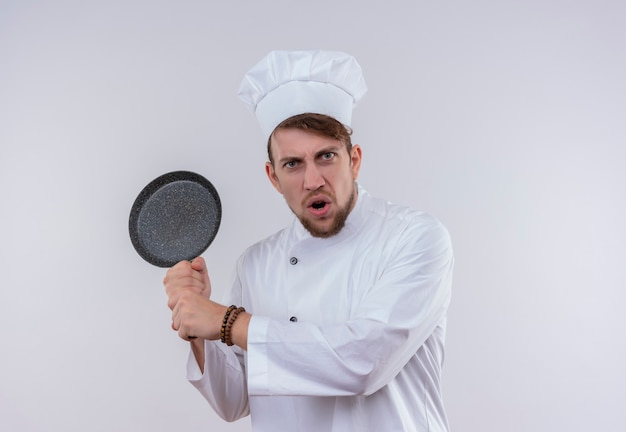 An angry bearded chef man wearing white cooker uniform and hat holding frying pan like a baseball bat on a white wall Free Photo