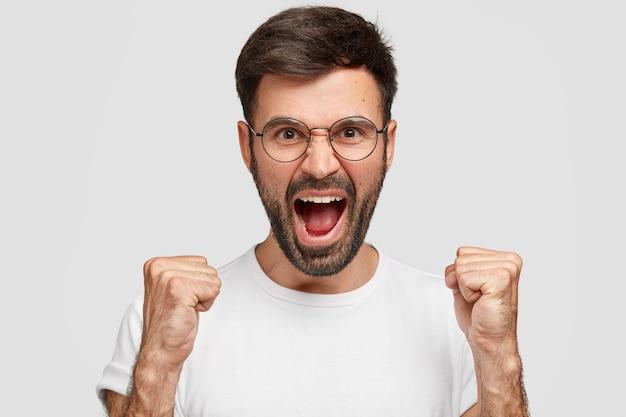 怒りの表情をした怒ったひげを生やした男は、怒りで眉を上げ、大声で叫び、カジュアルな白いtシャツを着て、不快感を表現し、狂気を感じ、壁に孤立します。音を立てないでください! 無料写真