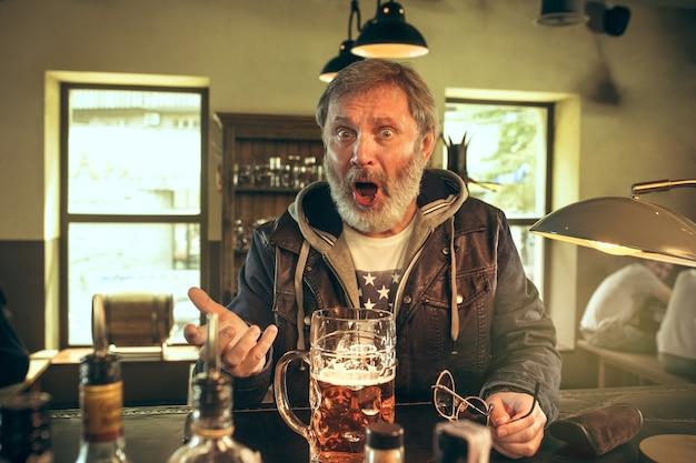 パブでアルコールを飲み、テレビでスポーツ番組を見ている怒っているひげを生やした男。私の好きなティームとビールを楽しんでいます。テーブルに座っているビールのマグカップを持つ男。サッカーやスポーツのファン。人間の感情の概念 無料写真