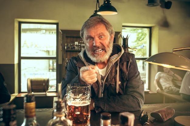 Uomo barbuto arrabbiato che beve alcolici nel pub e guarda un programma sportivo in tv. gustando il mio brulicare e la mia birra preferiti. uomo con boccale di birra seduto a tavola. appassionato di calcio o di sport. concetto di emozioni umane Foto Gratuite