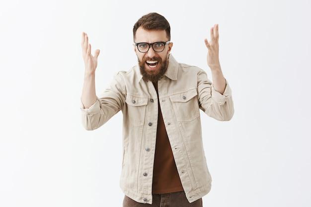 Злой бородатый мужчина в очках позирует у белой стены Бесплатные Фотографии