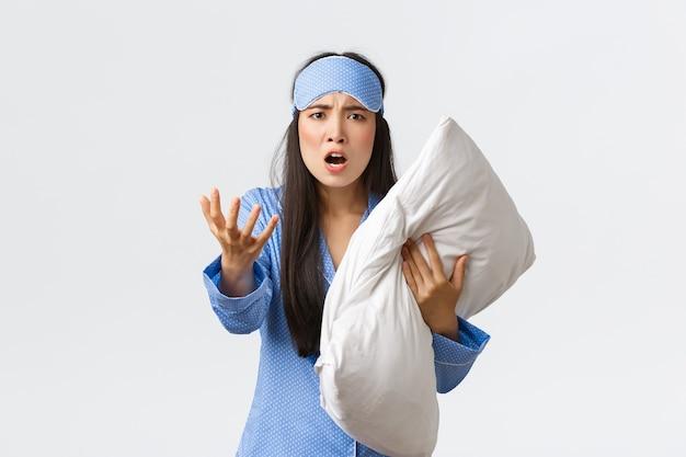 Злая обеспокоенная азиатская девушка с бессонницей в спальной маске и пижаме Premium Фотографии