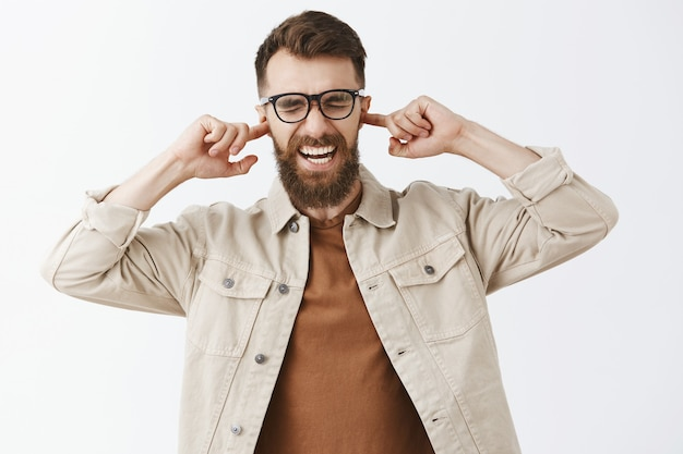 Angry bothered bearded man in glasses posing against the white wall Free Photo