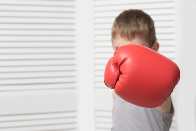 Angry boy in red boxing glove. hit Premium Photo