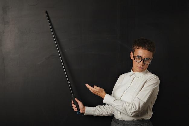 悪い感情とビジネススーツの怒っているブルネットのコーチは、折りたたみポインターと他の手で彼女の後ろの黒いチョークボードに表示されます。 無料写真