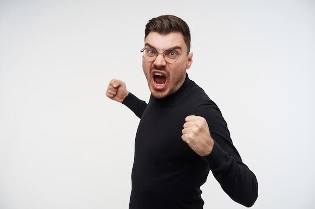 Maschio arrabbiato del brunette con taglio di capelli corto che urla follemente e stringendo le mani alzate in pugni Foto Gratuite