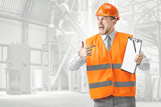 Il costruttore arrabbiato in una maglia della costruzione e in un casco arancione che grida. specialista della sicurezza, ingegnere, industria, architettura, manager, occupazione, uomo d'affari, concetto di lavoro Foto Gratuite