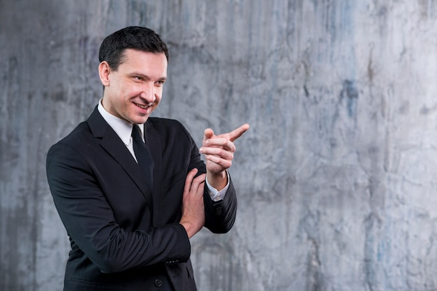 Angry businessman grinning and pointing away Free Photo