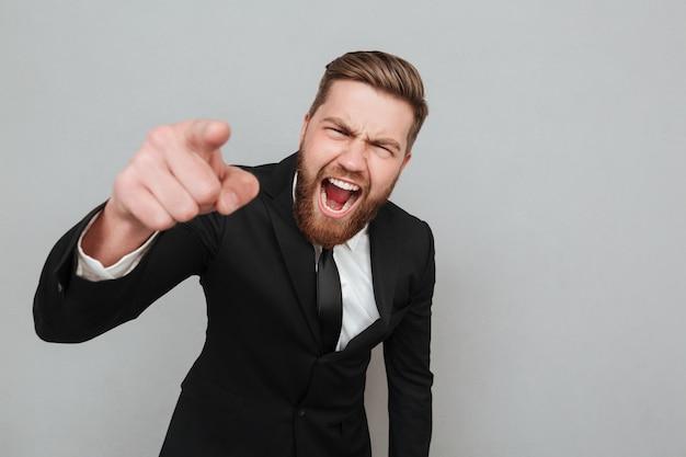Злой бизнесмен в костюме кричит и указывая пальцем Бесплатные Фотографии