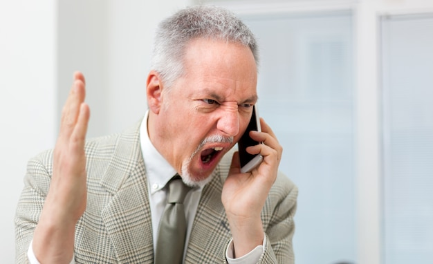 Angry businessman shouting on the phone Premium Photo