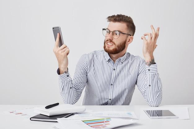 Uomo d'affari arrabbiato con acconciatura alla moda, indossa occhiali rotondi, guarda furiosamente nel telefono cellulare Foto Gratuite