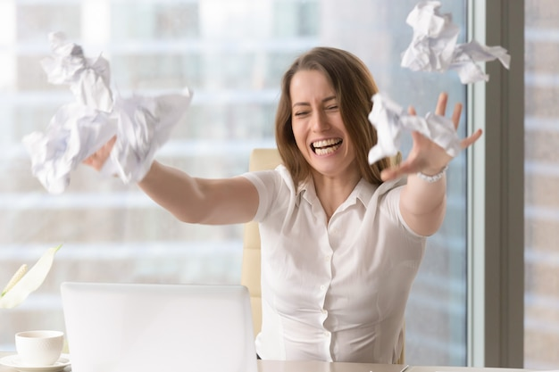 Angry businesswoman throwing crumbled papers Free Photo
