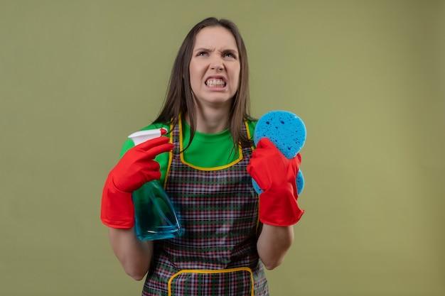 孤立した緑の壁にスポンジでクリーニングスプレーを保持している赤い手袋で制服を着て怒っているクリーニング若い女性 無料写真