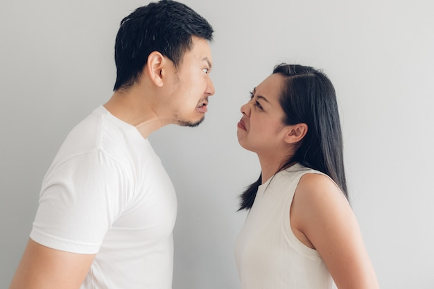 Angry couple lover in white t-shirt and grey background. Premium Photo