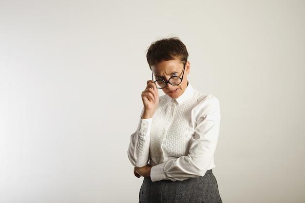 白い壁に彼女の丸い黒い眼鏡を調整する怒っている狂ったように見える先生 無料写真