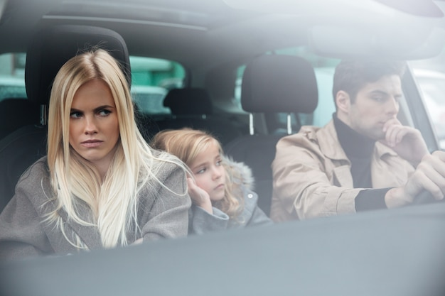 Angry displeased young family sitting in car after quarrel Free Photo