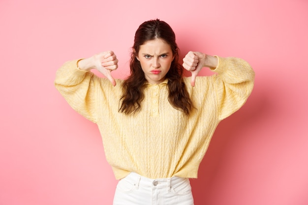Angry and displeased young girl frowning, showing thumbs down at something bad, express dislike, lea