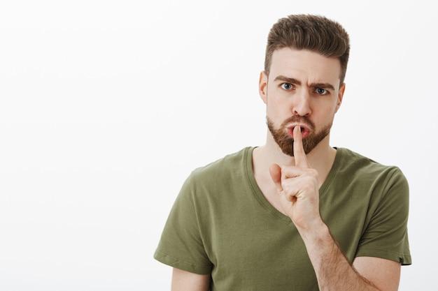 白い壁を越えてshhhをしている間口に人差し指を押しながら、口ひげを眉をひそめて怒っているように見えて怒って不機嫌な若い男は口を人差し指を押しながら話をしないでください 無料写真