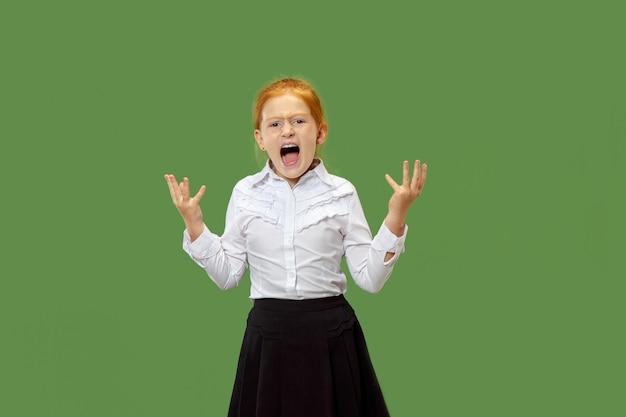Сердитая эмоциональная девушка кричит изолирована на зеленой стене Бесплатные Фотографии