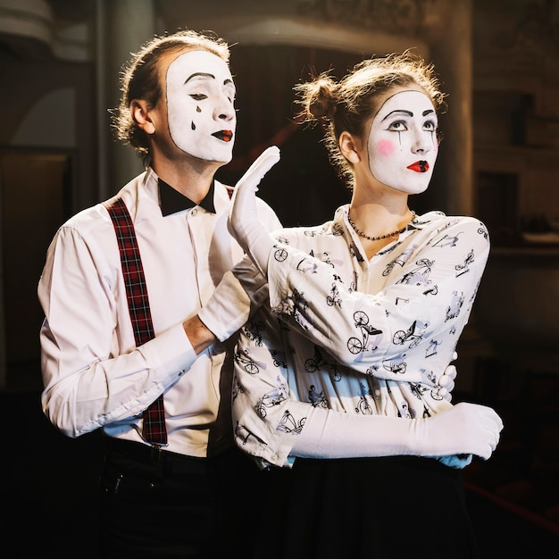 Angry female mime showing no hand sign to male mime standing behind him Free Photo