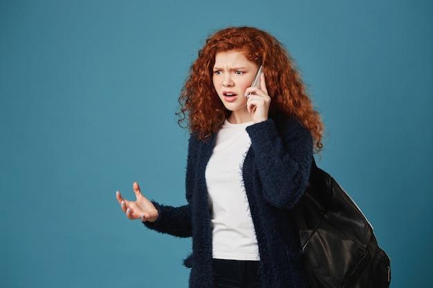 Donna arrabbiata dello studente bello che osserva da parte, gesticolando espressivo con le mani, discutendo con la madre di studio sul telefono. Foto Gratuite