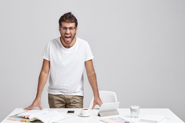 Impiegato maschio barbuto irritato arrabbiato in occhiali che grida, ha perso la calma Foto Gratuite