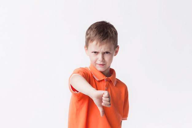 Angry little boy showing dislike gesture on white backdrop Free Photo
