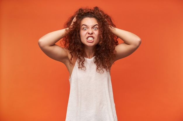 Angry looking woman, crazy girl with curly ginger hair. wearing white off-shoulder blouse. touching her head, terrible headache. isolated over orange wall Free Photo