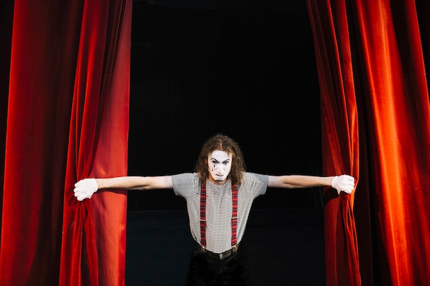 Angry male mime artist holding red curtain Free Photo