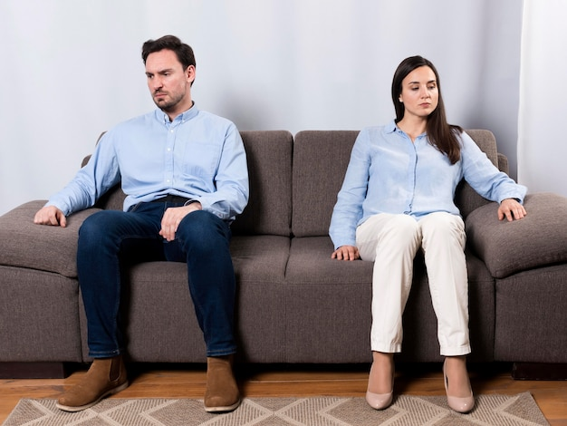 Angry male and woman sitting on the couch Free Photo