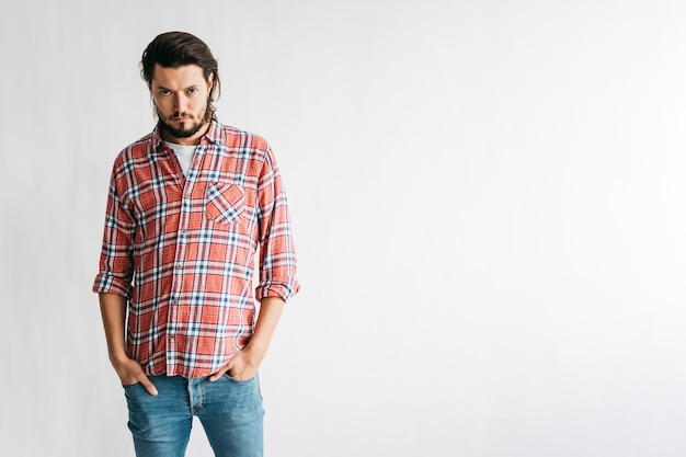An angry man in checkered shirt with two hands in his pocket isolated on white background Free Photo