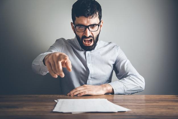Злой человек вручает документ на столе Premium Фотографии