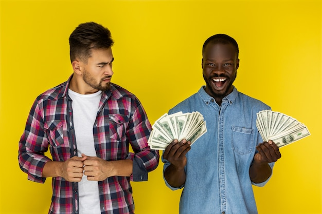 Angry man and happy man holds dollars Free Photo