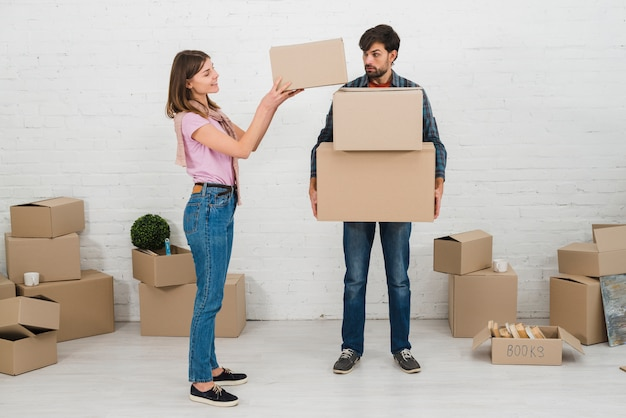 Angry man looking at her wife stacking the cardboard boxes over his hands Free Photo