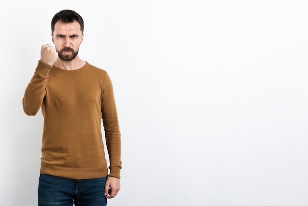 Angry man posing with fist up Free Photo