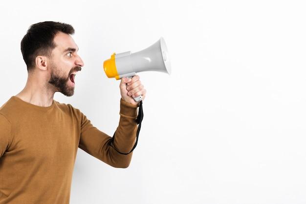 Angry man screaming in megaphone Free Photo