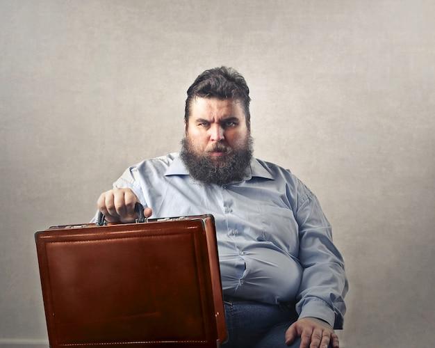 Uomo barbuto più grande arrabbiato che si siede e che tiene una valigetta in grembo Foto Gratuite