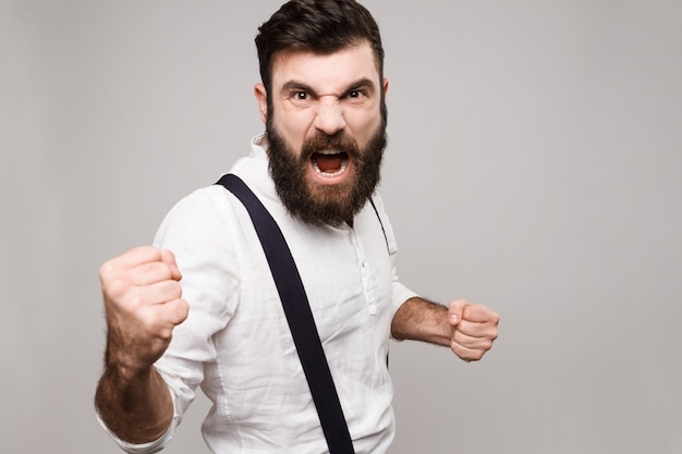 Angry rude young handsome man shouting over white. Free Photo