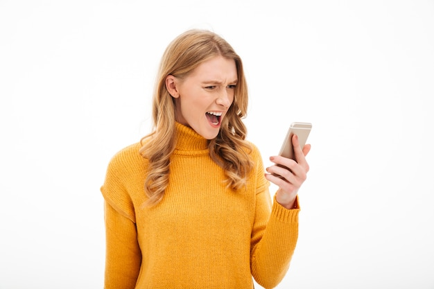 Angry screaming young woman using mobile phone. Free Photo