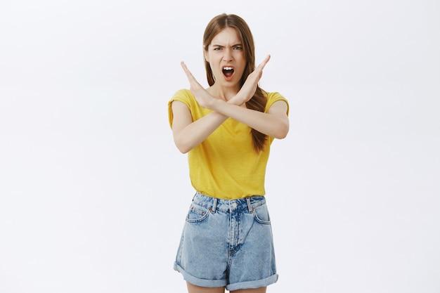 Сердитая серьезная молодая девушка делает крестный жест, приказывает остановиться, говорит нет, запрещает действия Бесплатные Фотографии
