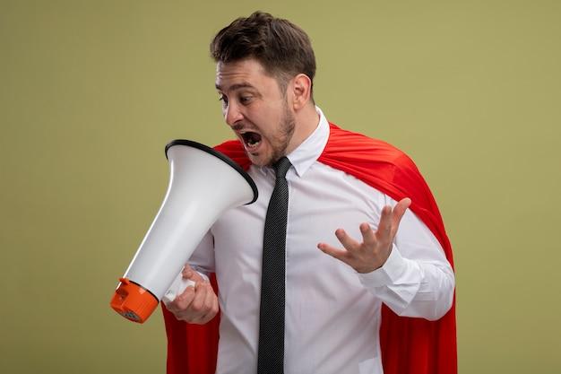Злой супергерой бизнесмен в красной накидке кричит в мегафон с агрессивным выражением лица с протянутой рукой, стоя на зеленом фоне Бесплатные Фотографии